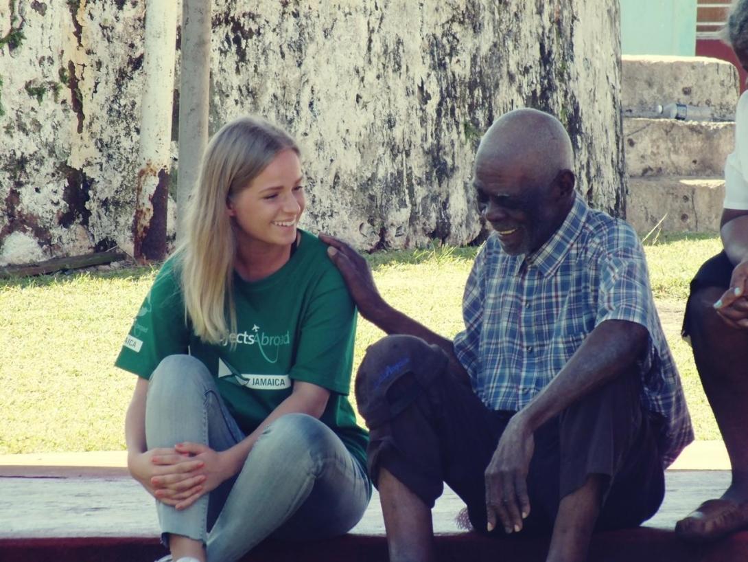 ジャマイカの老人と交流するボランティア